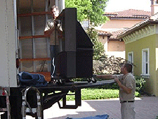 a large tv on a truck lift gate getting moved